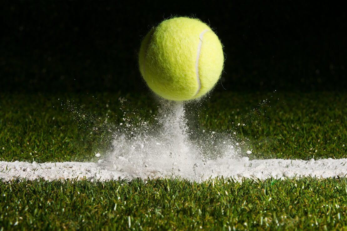Ball landet auf der Linie auf dem Rasen und wirbelt das Pulver hoch
