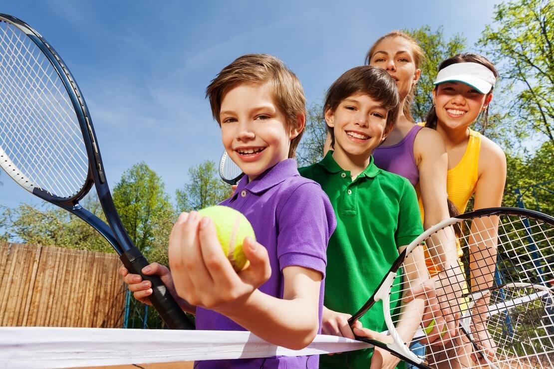 Vier Kinder stehen hintereinander mit einem Tennisball und Schläger