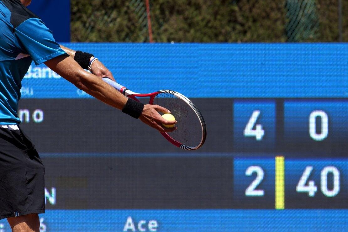 Spieler schlägt einen Tennisball