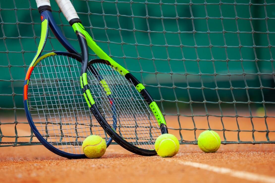Tennisschläger lehnen am Netz